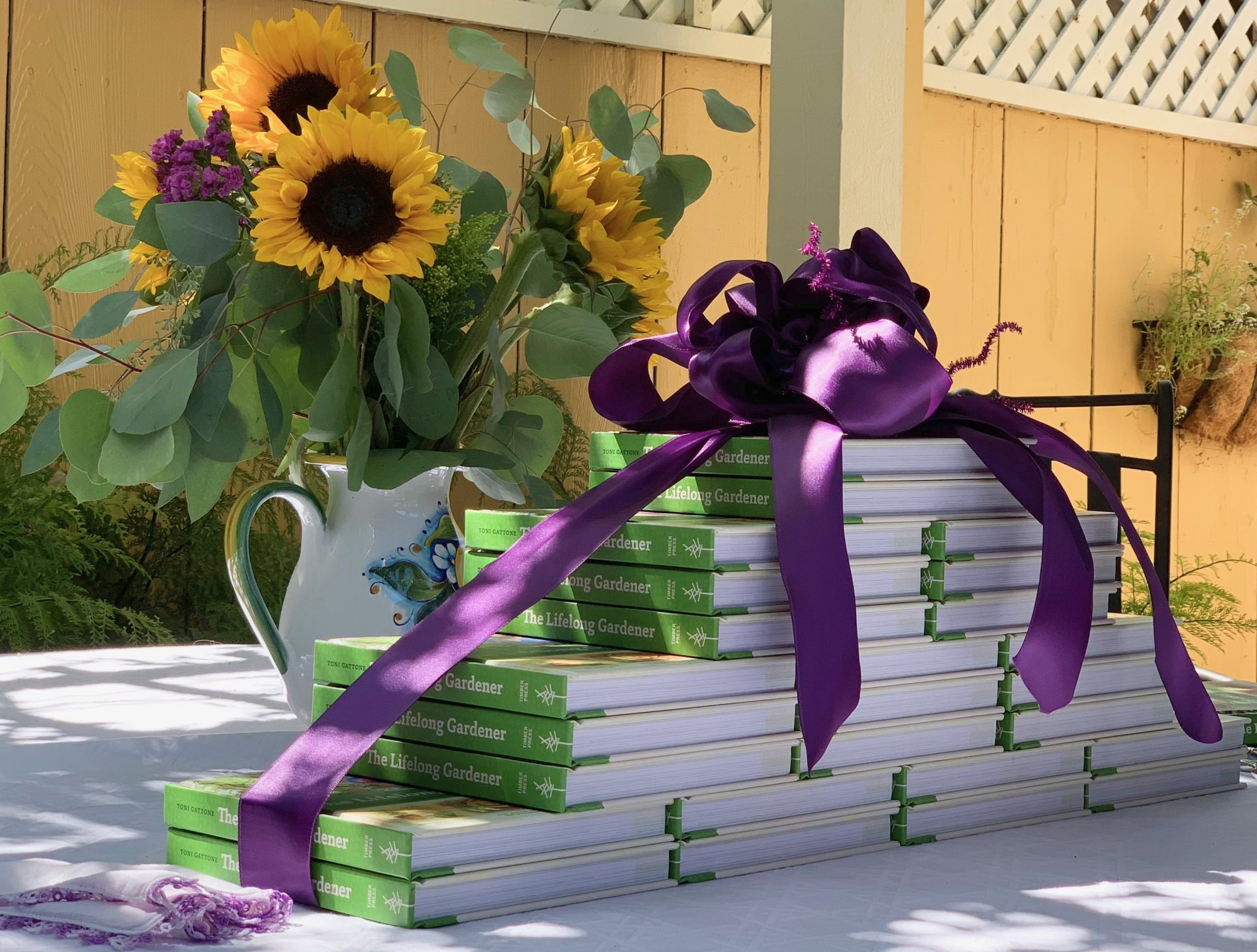 Sunflowers surround copies of The Lifelong Gardener at book release event with Toni Gattone